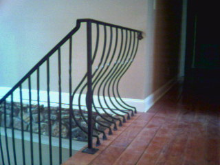 wrought iron interior railing with belly picket design