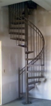 ornamental iron spiral stairway with forged twist pickets on handrail